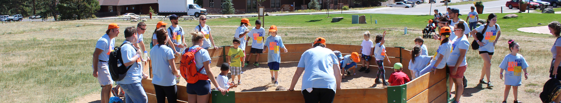 A group of children and adults play in a sandbox