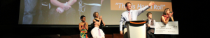 6 people stand on a stage to review an award check for the Film Festival Contest